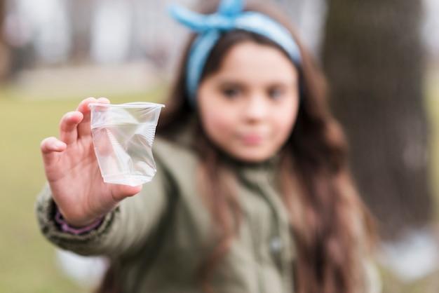 Copo plástico de close-up com menina desfocado