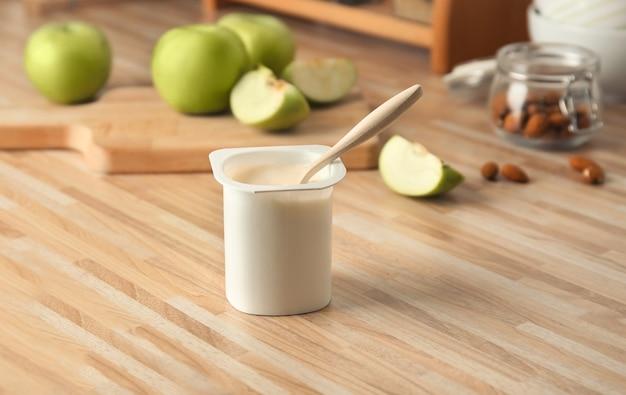 Copo plástico de iogurte saboroso na mesa de madeira