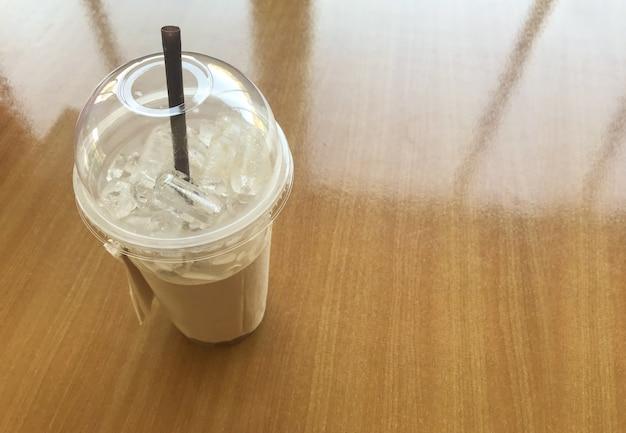 Copo plástico vazio do café de gelo no fundo de madeira da tabela da reflexão da janela.