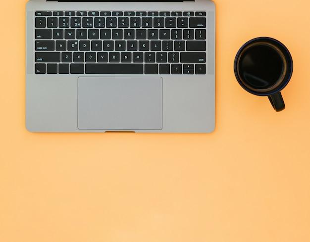 Copo preto com café e um laptop cinza em uma superfície laranja