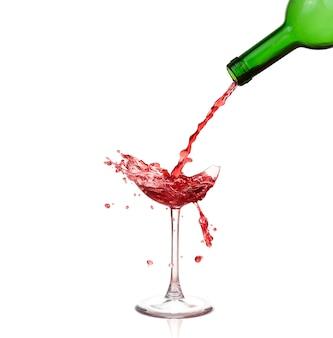 Copo quebrado com vinho e gotas, isolado no branco