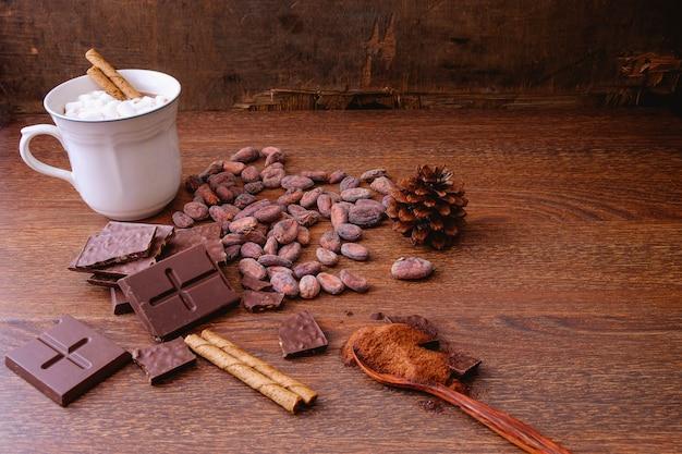 Copo quente do cacau com barras de chocolate e feijões de cacau.