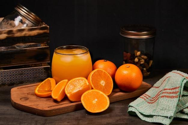 Copo refrescante com suco de laranja fresco, gelo e laranjas em uma mesa de madeira em fundo escuro