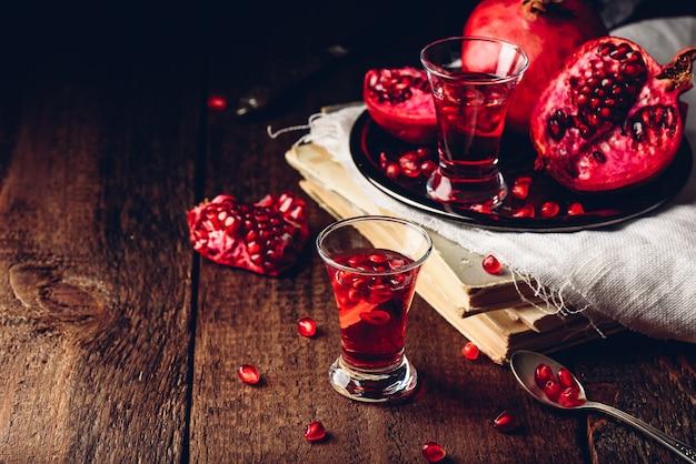 Copo shot de cocktail de romã com vodka, sumo e frutas frescas