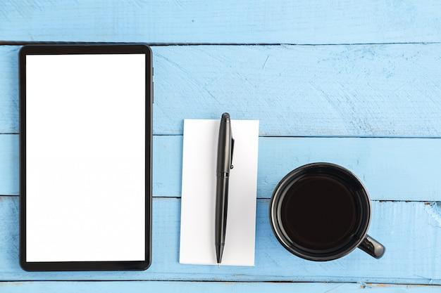 Copo, tablet, caderno de papel pequeno e uma caneta preta em uma madeira azul
