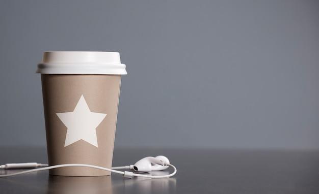 Copo térmico de chá na mesa com fones de ouvido