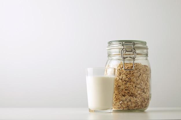 Copo transparente com leite orgânico fresco perto de jarra rústica com aveia em flocos isolada lateralmente na mesa branca