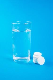 Copo transparente de água e comprimidos efervescentes solúveis isolados em azul
