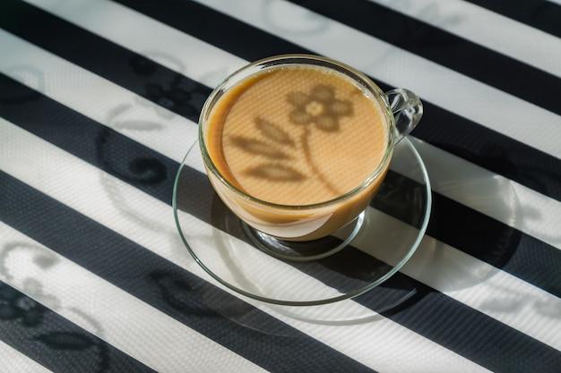 Copo transparente de café cremoso em fundo escuro. luz solar e sombras duras. imagem enfraquecida com espaço de cópia