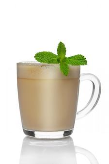 Copo transparente de cappuccino com licor de menta, isolado no branco