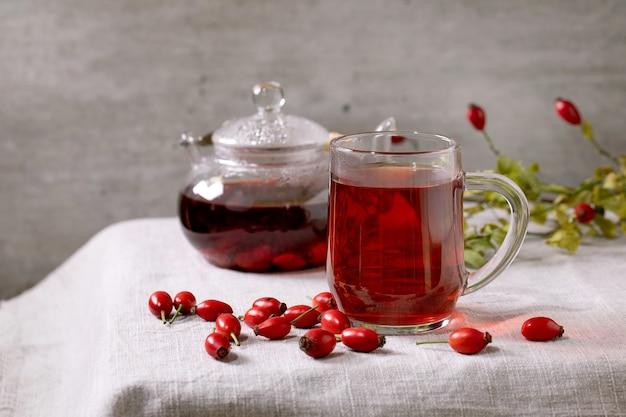 Copo transparente de chá de ervas de bagas de rosa mosqueta e bule de vidro em pé na toalha de mesa de linho branco com frutas silvestres de outono ao redor. bebida quente aconchegante de inverno