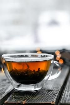 Copo transparente de chá na madeira
