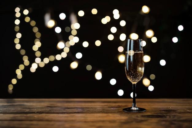 Copo transparente de champanhe com efeito bokeh