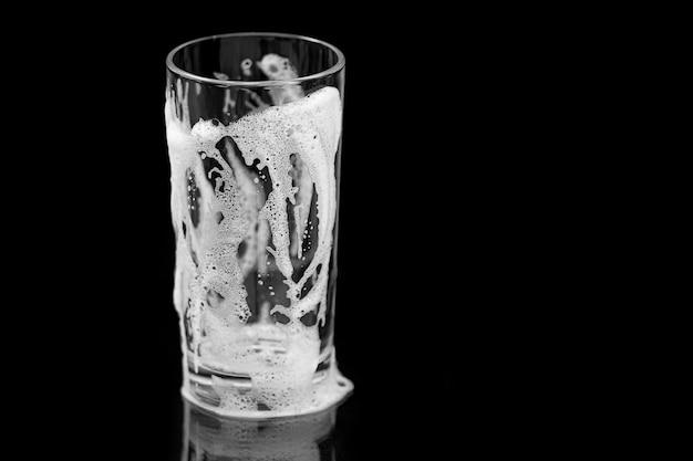 Copo vazio com espuma, copo limpo com bolhas e gotas isoladas no fundo preto