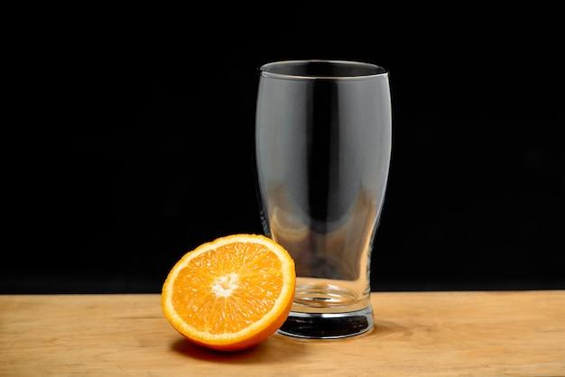 Copo vazio com meia laranja na mesa de madeira