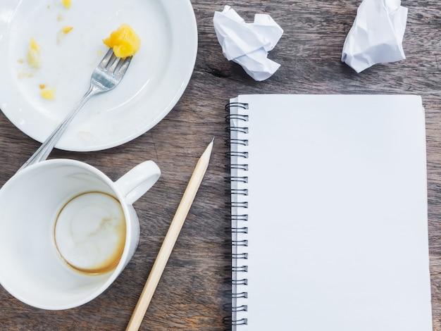Copo vazio de café e prato com o bloco de notas
