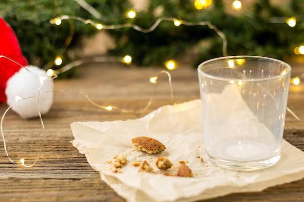 Copo vazio de leite e migalhas de biscoitos para o papai noel na frente de um bokeh de luzes de árvore de natal. conceito de ano novo.