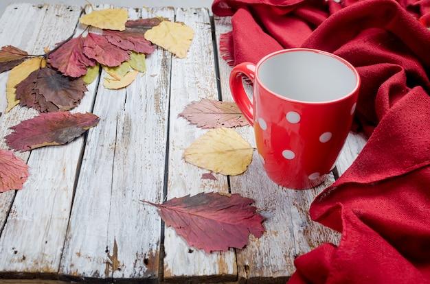 Copo vazio para o chá, folhas vermelhas secas no dia do outono