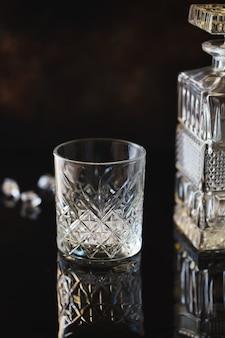 Copo vazio para uísque ou bourbon com uma garrafa quadrada de cristal