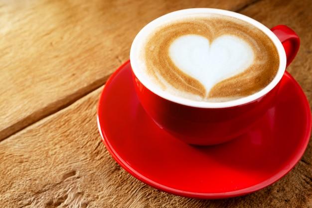 Copo vermelho, café com leite café em forma de coração na mesa de madeira