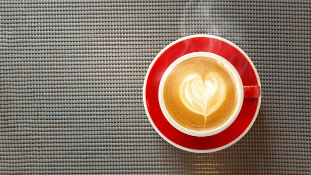 Copo vermelho, café com leite café em forma de coração na toalha de mesa de madeira