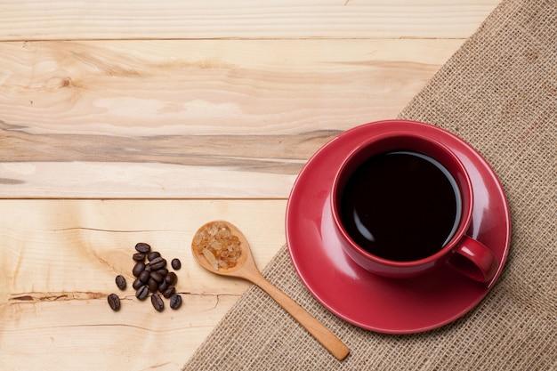 Copo vermelho café e açúcar em colher no feijão de café de serapilheira na placa de madeira