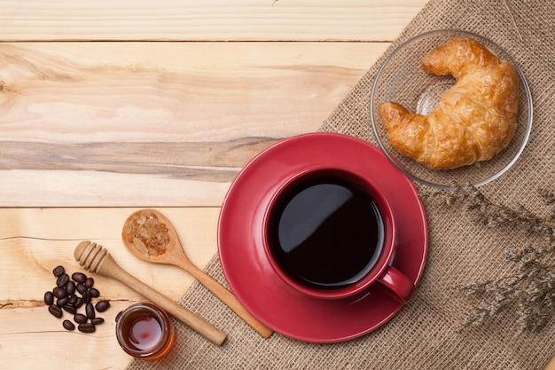 Copo vermelho café e açúcar na colher na serapilheira, grão de café na madeira mel e croissant flor seca