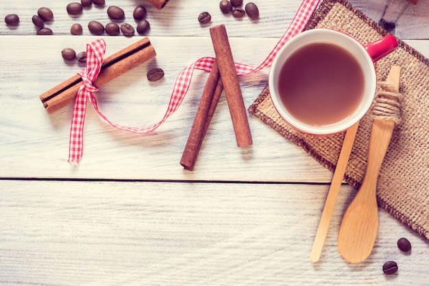Copo vermelho com café expresso, canela e colher
