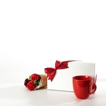 Copo vermelho com caixa de presente e rosas em branco