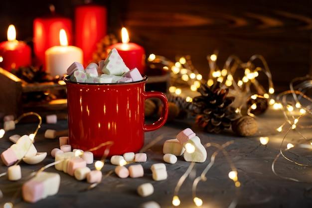 Copo vermelho com chocolate quente e marshmallow em bokeh. conceito de ano novo. cartão de felicitações.