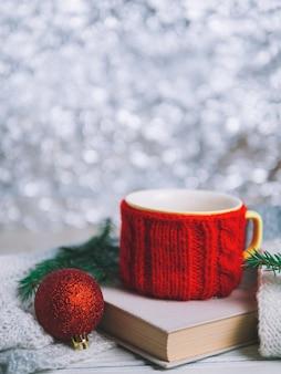 Copo vermelho de chá ou café com livro e galhos de árvores de natal