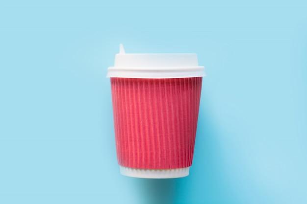 Copo vermelho de papel descartável com uma tampa plástica branca para o café ou o chá quente no azul.
