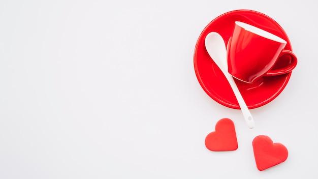 Copo vermelho e prato com colher perto de corações de ornamento