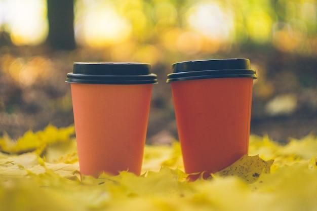 Copos afastados do café em uma folha do outono. café ao ar livre.