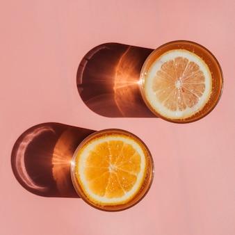 Copos cheios de água e fatias de laranja vista superior