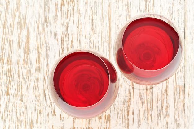 Copos cheios de vinho tinto em uma mesa de madeira branca, vista superior