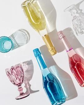 Copos coloridos para vinho e garrafa com espumante com luz solar