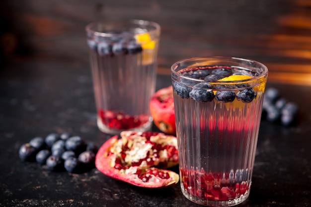Copos com água desintoxicante feita de berry orgânico e romã em fundo escuro de madeira vintage