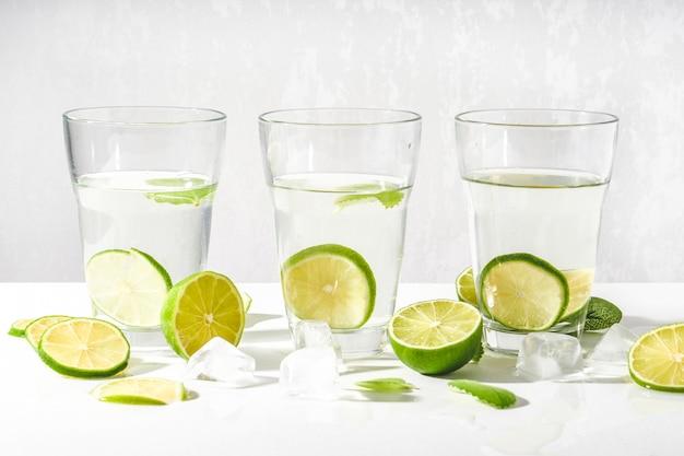 Copos com água, rodelas de limão, hortelã e cubos de gelo