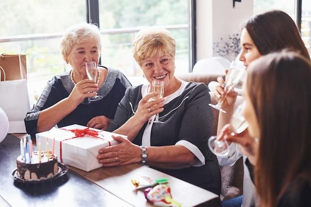Copos com álcool nas mãos e bolo na mesa. mulher sênior com família e amigos comemorando um aniversário dentro de casa.