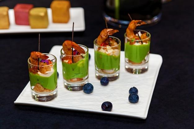 Copos com aperitivos de frutos do mar e massas verdes em travessa de banquete para eventos e buffet catering