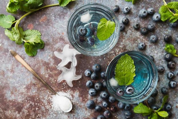 Copos com bebidas refrescantes de hortelã de mirtilo