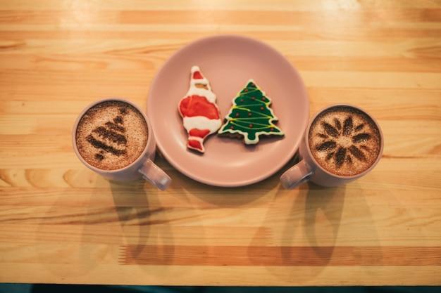 Copos com carrinho de café em ambos os lados do prato com gingerbreads de natal