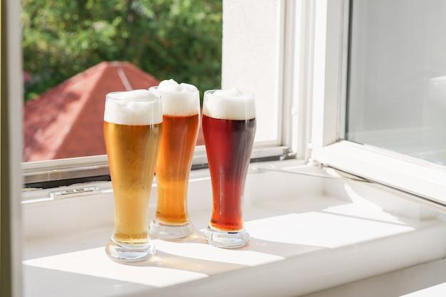 Copos com cerveja no parapeito da janela e janela aberta em dia de sol. luz natural. oktoberfest. novo conceito de normal e estilo de vida