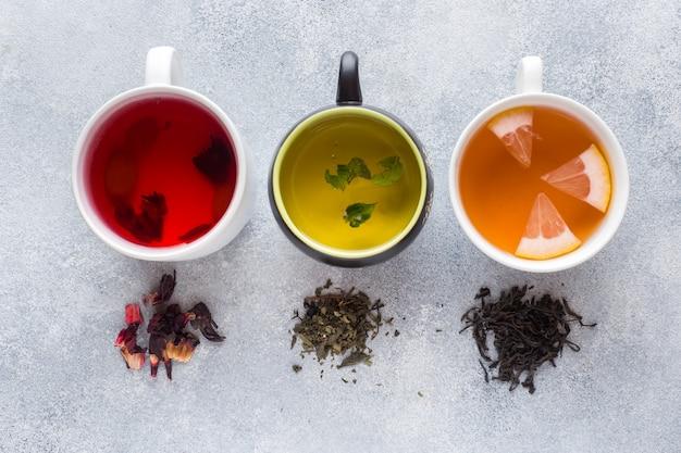 Copos com chá diferente vermelho, verde e preto na mesa cinza