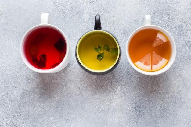 Copos com chá diferente vermelho, verde e preto na mesa cinza.
