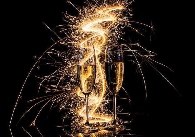 Copos com champanhe à luz das luzes de bengala