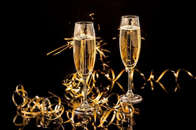 Copos com champanhe contra luzes do feriado