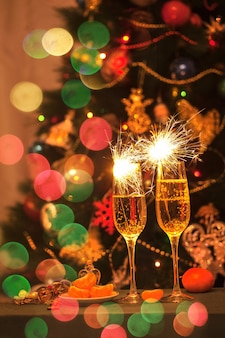 Copos com champanhe e espumantes no fundo de uma árvore de natal decorada