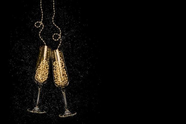 Copos com champanhe em fundo preto. celebração de natal e ano novo